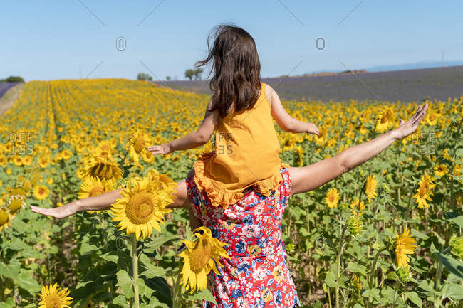 Mother carrying daughter on shoulders in sunflower field during summer