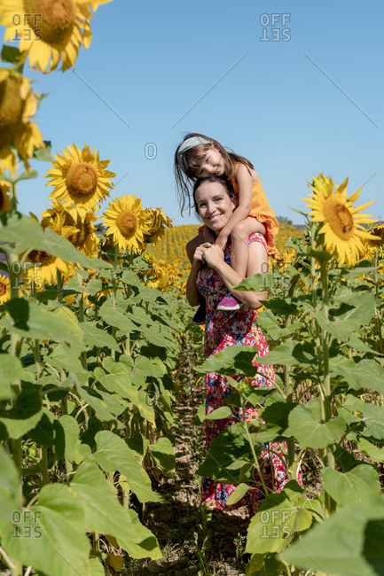 Smiling mother carrying daughter on shoulders in sunflower field