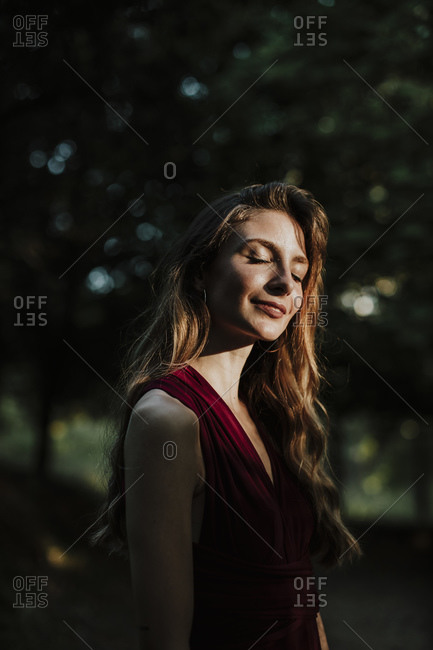 Beautiful woman with eyes closed standing in forest