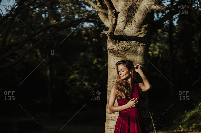 Smiling woman with eyes closed standing against tree trunk in forest