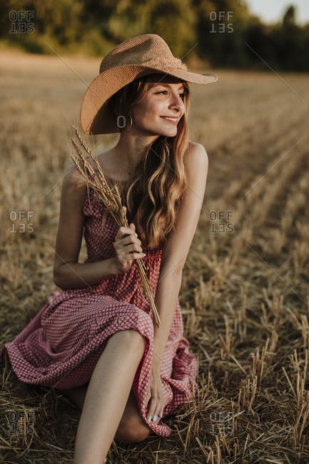 Happy woman sitting while looking away in wheat field during sunset