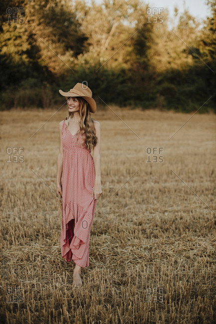 Woman wearing dress looking away while walking in wheat field during sunset