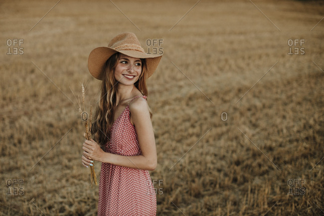 Woman looking over shoulder while holding wheat crop standing in farm