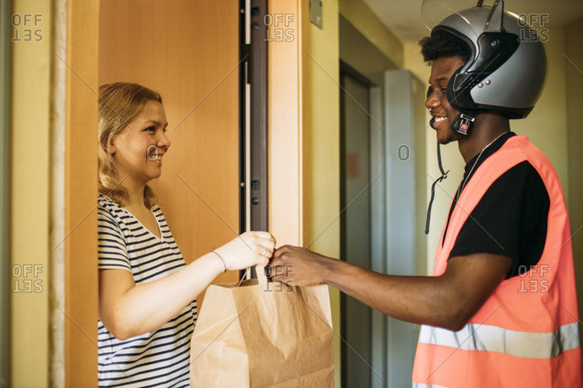 Woman taking paper bag from delivery man with protective mask