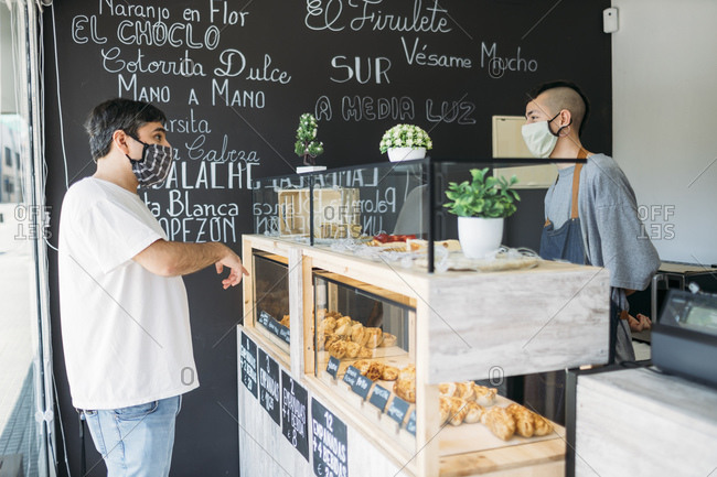Waiter and customer with protective masks at the counter in a cafe