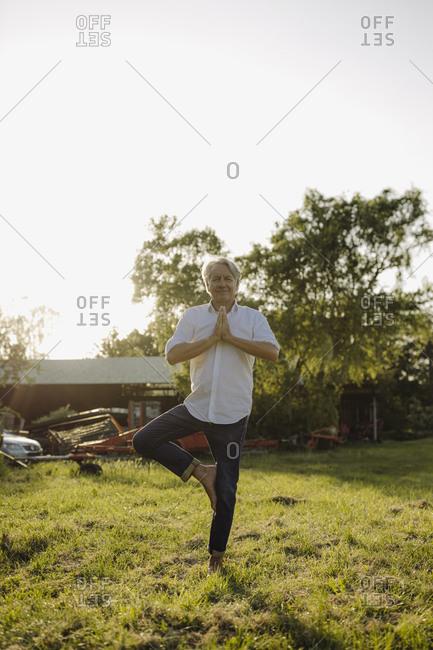 Man doing yoga on one leg against clear sky in yard