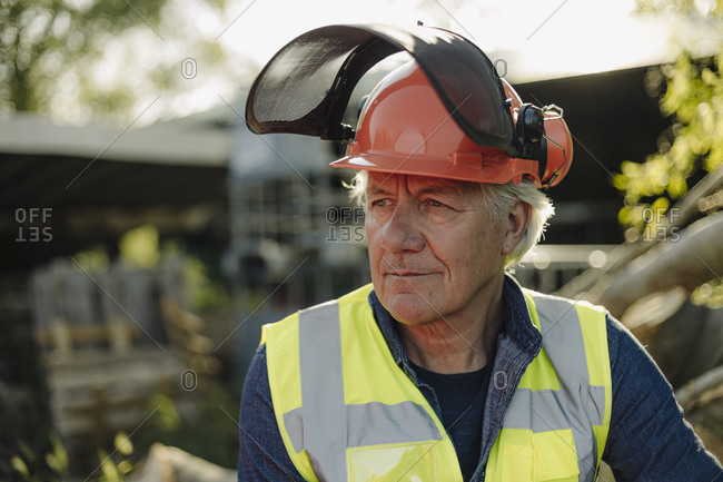 Wrinkled man wearing protective workwear looking away in forest
