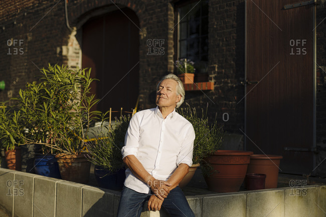 Contemplating man with eyes closed sitting on retaining wall in yard