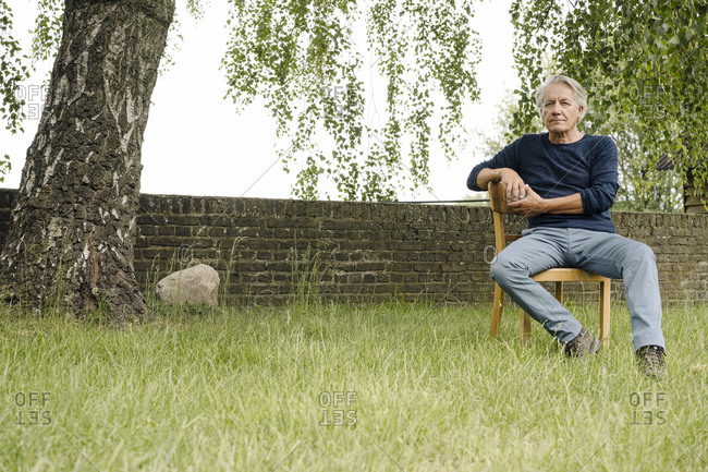 Contemplating man sitting on chair against brick wall in backyard