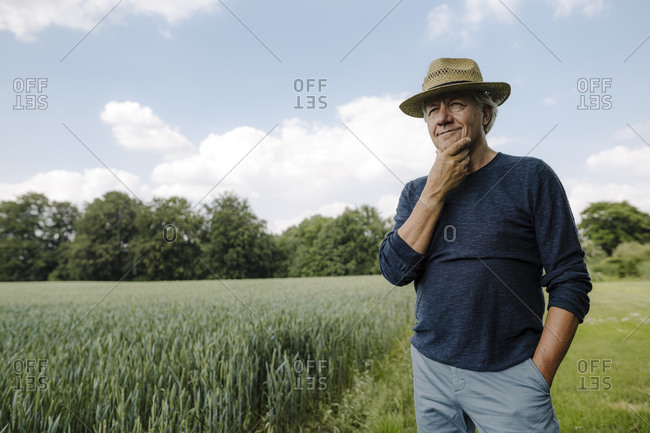 Contemplating man looking away with hand on chin while standing against sky in field