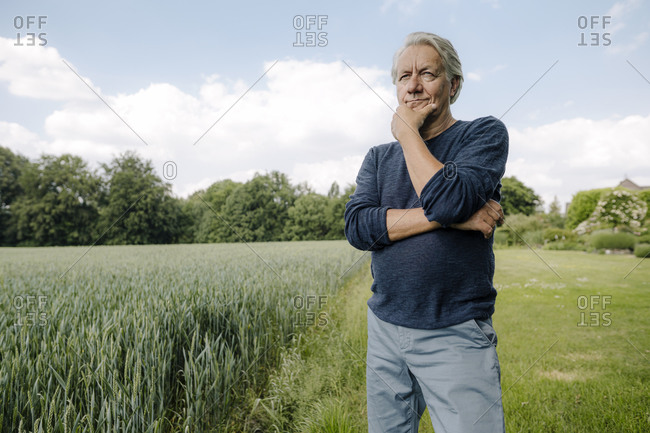 Wrinkled man looking away with hand on chin while standing against sky in field