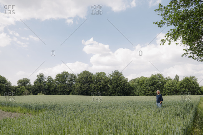 Man with hands in pockets standing in agricultural field