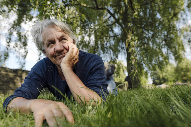 Confident smiling man lying on front in field