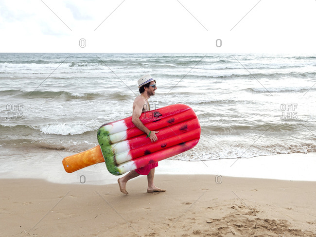 Man walking with airbed on the beach
