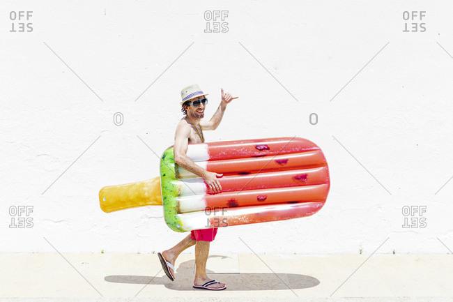Smiling man making hang loose sign holding airbed walking on sidewalk