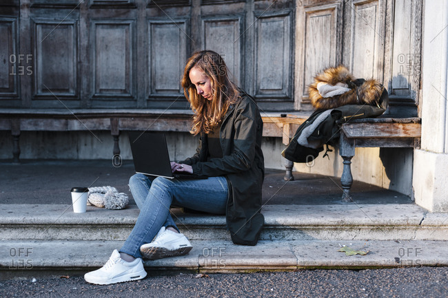 Businesswoman sitting at park while working on laptop
