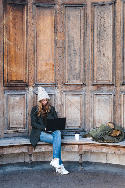 Businesswoman sitting on bench while using laptop at park