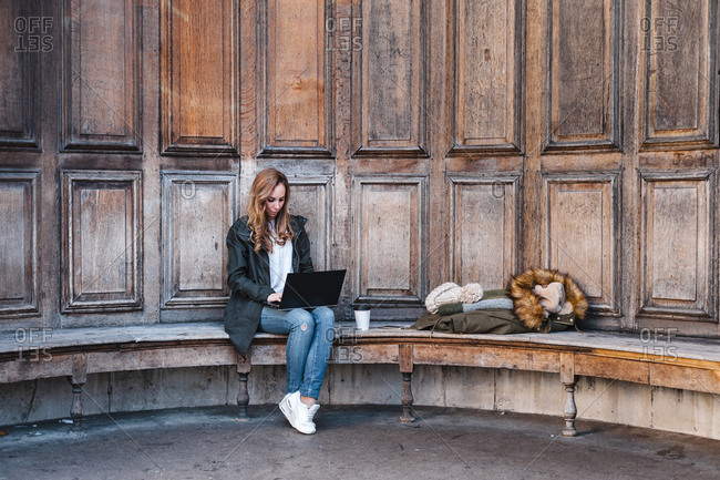 Beautiful businesswoman using laptop while sitting on park bench against wooden wall