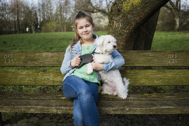 Smiling girl with dog sitting on bench in park
