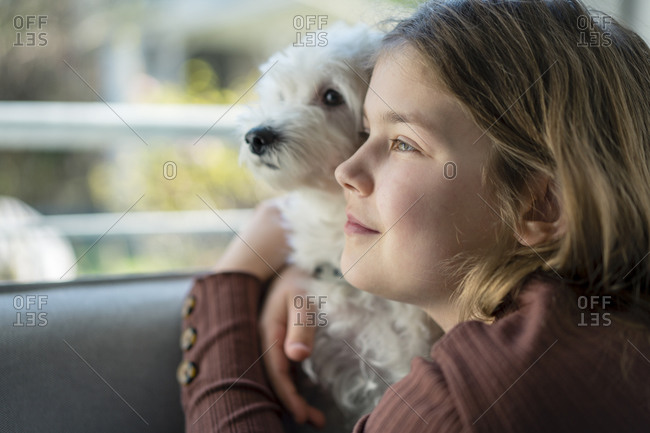 Cute girl embracing dog while looking away in living room