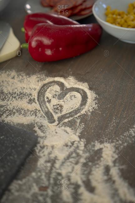 Heart shape drawn on flour over kitchen island