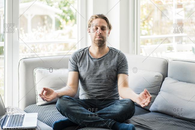 Male freelancer meditating by laptop on sofa