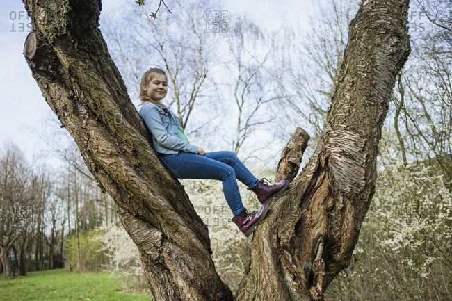 Smiling girl balancing over tree trunk in park
