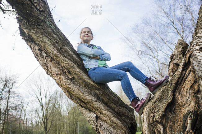 Smiling girl with arms crossed leaning on tree trunk in park