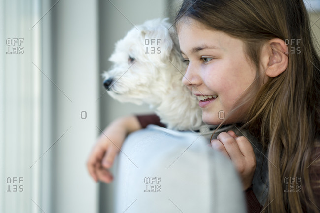 Cute smiling girl with dog looking away in living room