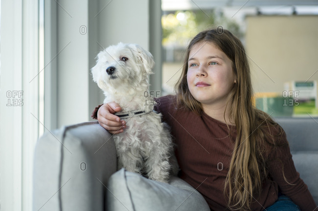 Cute girl with dog looking away in living room