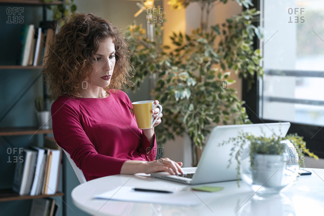 Beautiful young businesswoman holding coffee cup while using laptop at home office desk