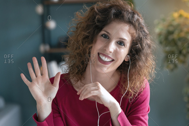 Smiling businesswoman wearing headphones while waving at home