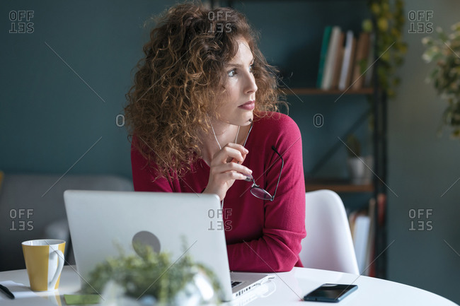 Contemplating young businesswoman looking away while sitting with laptop at home office desk