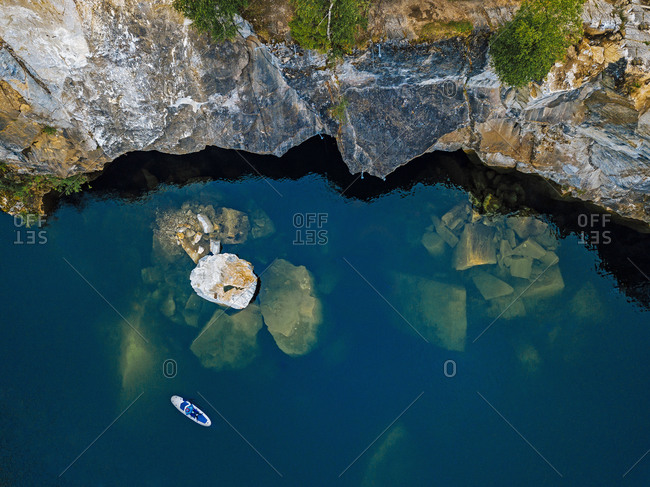 Aerial view of paddleboarder surfing over marble boulders sunken in Marble Lake