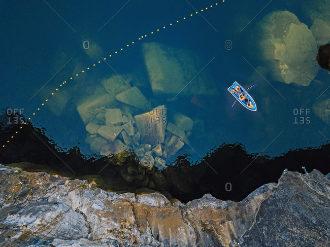Aerial view of boat sailing over marble boulders sunken in Marble Lake