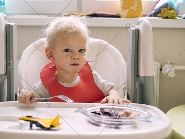 Baby boy sitting on high chair while eating breakfast in kitchen
