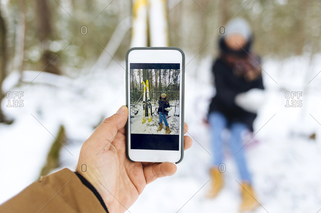 Man photographing girlfriend by skis through smart phone in forest during winter