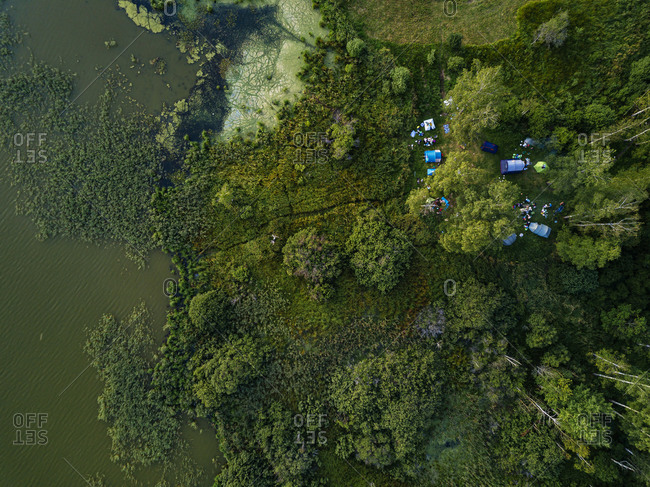 Aerial view of tents pitched on green shore of Torbeyevskoye lake