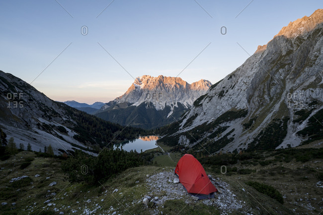 Tent pitched in mountain valley at dusk with Seebensee in background