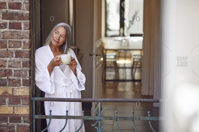 Smiling woman drinking tea while standing in balcony