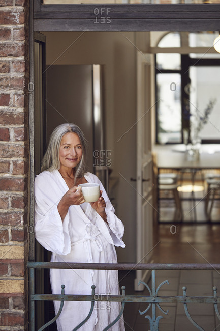 Smiling woman drinking tea in balcony