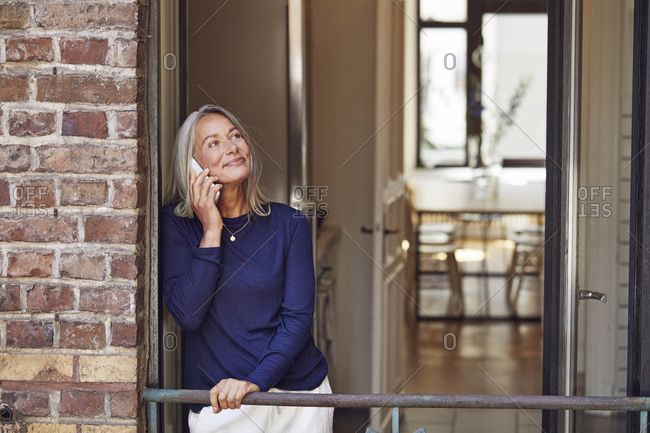 Smiling woman talking on phone in balcony