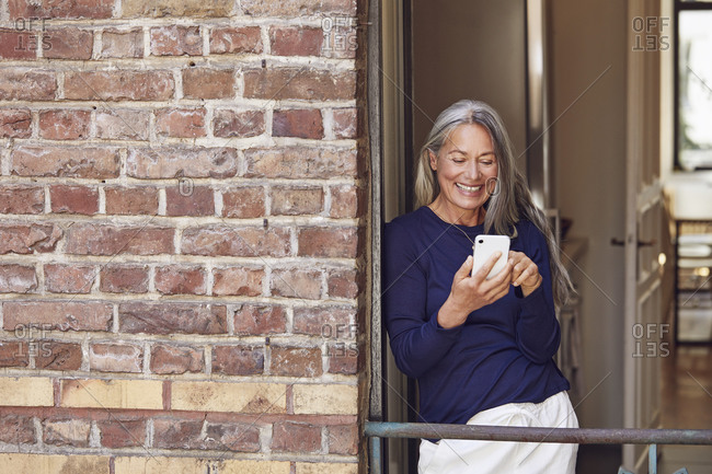 Smiling woman using phone in balcony