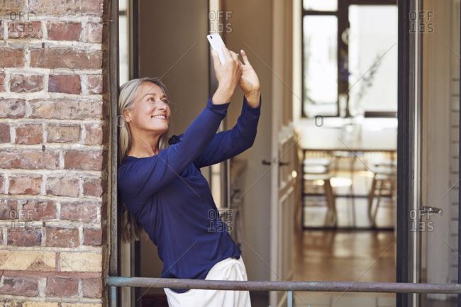 Smiling woman taking selfie through smart phone in balcony