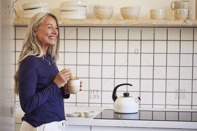 Smiling woman drinking tea while standing in kitchen