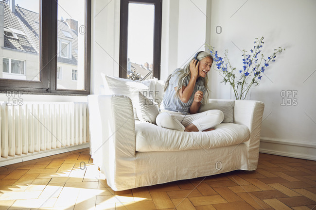 Happy woman listening to music on sofa at home