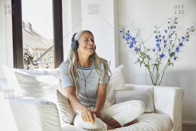 Happy woman listening to music through headphones on sofa at home