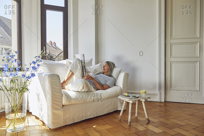 Woman reading magazine over sofa in living room