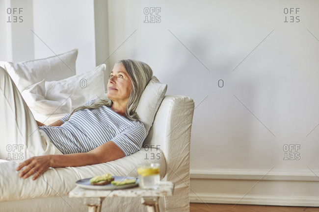 Contemplating woman looking away over sofa in living room