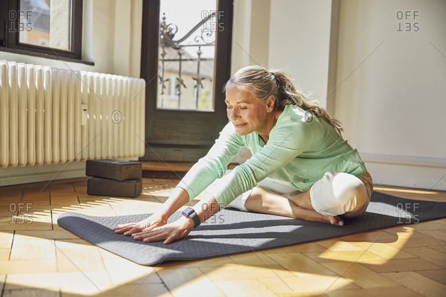 Woman exercising while sitting on exercise mat over floor in living room